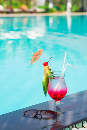 chilled out: Vertical image of a glass of fresh cocktail with a pineapple slice near the swimming pool