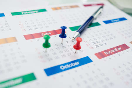 important date: Close-shot of a business calendar with important dates being marked with colorful pins