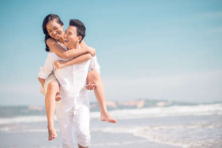 Close up image of a young funny couple piggybacking on the beach Stock fotó