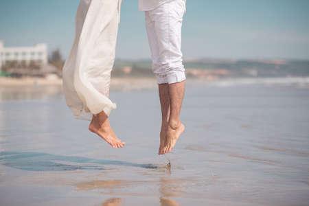 brincando: Imagen recortada de una pareja saltando juntos en la playa