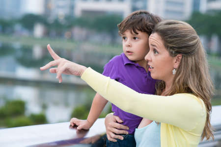 Close up image of a mother holding her son on hands and pointing at something in the street