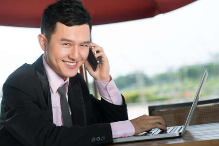Portrait of a toothy entrepreneur receiving an important call from a client Stock Photo