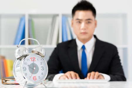 puntualidad: Imagen de un hombre de negocios preocupado con un reloj de alarma en el primer plano Foto de archivo