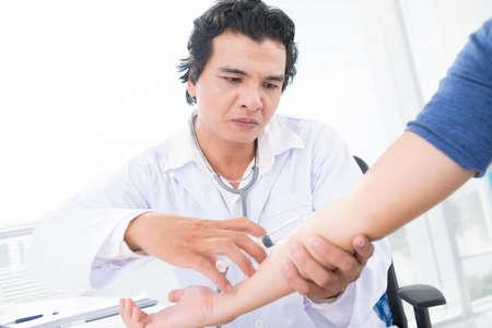 koncentrovaný: Zkušený imunolog, který podává injekci pacientovi