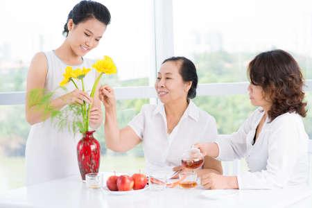 mujeres sentadas: Tres mujeres asiáticas sentado en la mesa