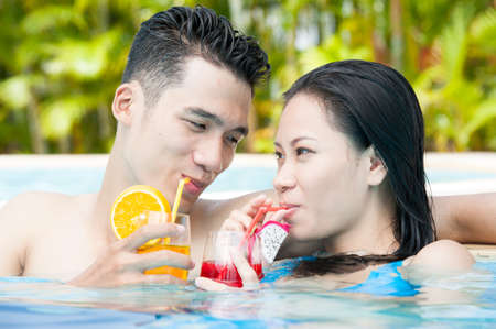 resort life: Couple of young people in swimming pool drinking juice Stock Photo
