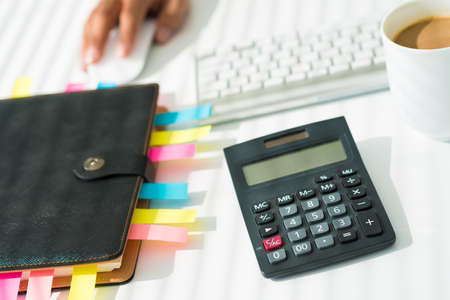 estimating: Close-up of a business workplace with an organizer, a calculator and a cup of coffee Stock Photo