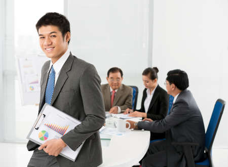 asian business meeting: Smiling businessman standing with clipboard in hands Stock Photo