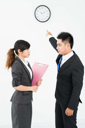 denote: Businessman showing at clock for his colleague