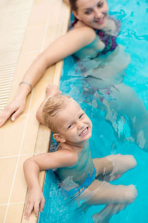Mother and little kid relaxing in a swimming pool Stock Photo