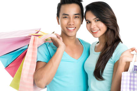 or spree: Close up of a young couple with shopping-bags