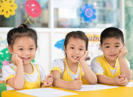 Asian children sitting behind the desk in the room