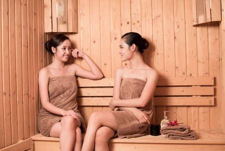 Zwei Frauen sitzen in der Sauna und reden miteinander