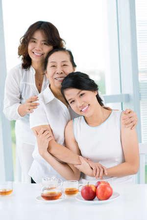 Drie Aziatische vrouwen die zich achter de lijst bevinden Stockfoto