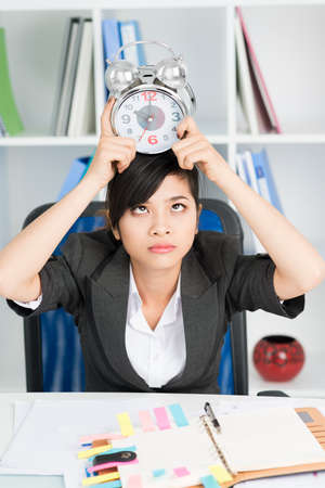 nuda: Tired asian businesswoman holding alarm on head