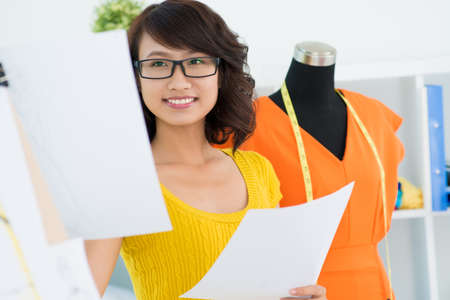 drafts: Asian designer smiling and holding drafts Stock Photo