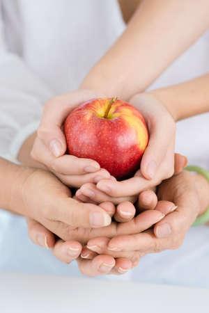 Red apple in three women?s hands