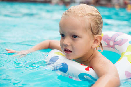Cute little boy swimming with a help of a life saver Stock Photo
