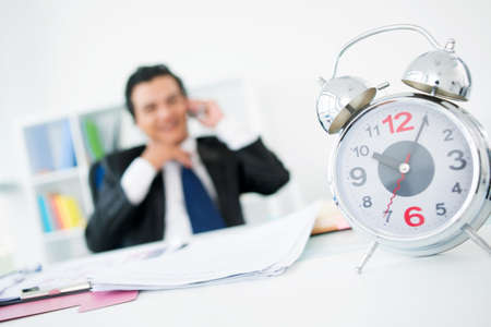 Happy businessman talking by the phone in his office while time ticking away on the clock