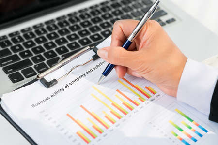memorise: Close up of businessperson analyzing statistical data Stock Photo