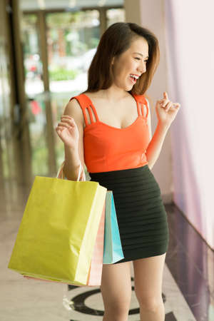Vertical image of an attractive young woman in the shopping mall Stock Photo