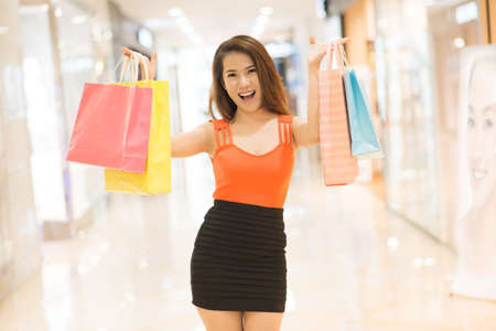 Portrait of an excited woman showing her shopping-bags in the mall Stock Photo