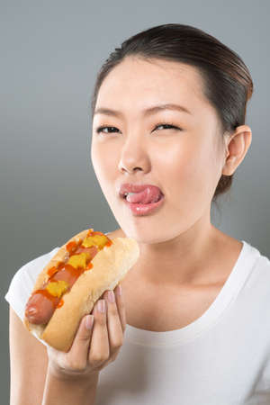 hot asian: Vertical portrait of a pretty Asian girl licking her lips before tasting a hot dog
