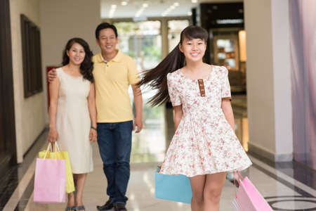 focus on foreground: Portrait of a female teenager at shopping with her parents  Stock Photo