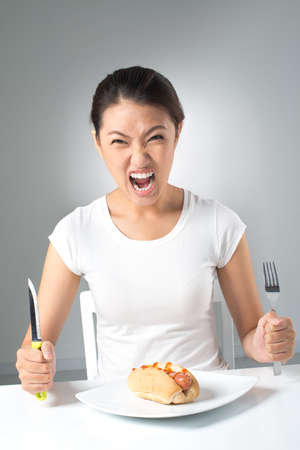 hot temper: Imagen vertical de una chica loca pidiendo más comida rápida Foto de archivo