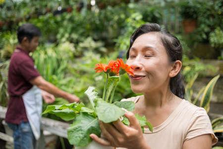 landlady: Close-up of a senior woman enjoying the flower's fragrance on the foreground