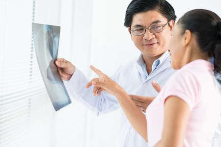 Bild eines Doktors, der einen Röntgenstrahl mit einem weiblichen Patienten überprüft