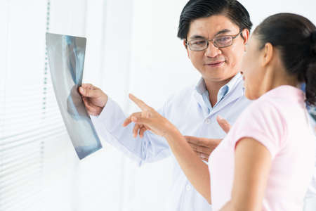 Image of a doctor examining an x-ray with a female patient Stock Photo
