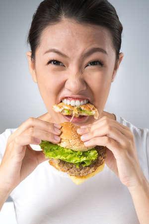 niña comiendo: Vertical shot of a wild hamburger eater taking a huge bite