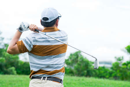A golfer playing golf viewed behind outdoors