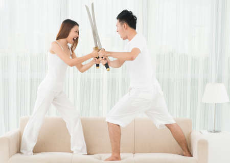 Full-length image of a young couple fighting with swords on the sofa at home