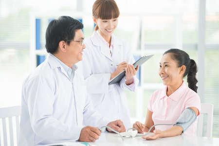 의사와 그의 간호사가 병원에서 수석 환자를 검사의 이미지 스톡 콘텐츠