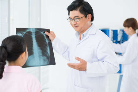 Image of an adult doctor showing an x-ray to the patient on the foreground