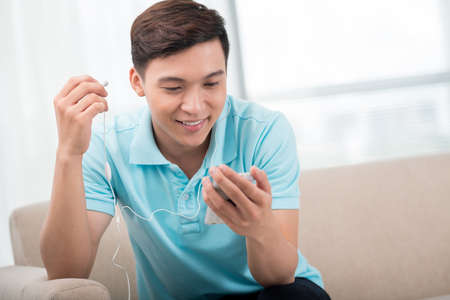 cool guy: Excited guy being about to listen to a cool new song on his mp3-player Stock Photo