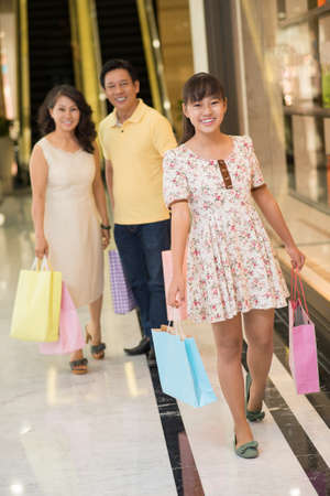 Full-length portrait of a teenager with shopping bags walking with her family in the mall on the foreground