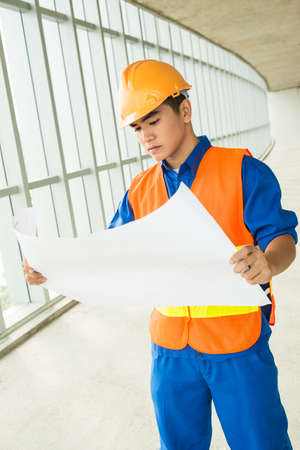Vertical image of a constructor worker standing with a blueprint inside Stock Photo