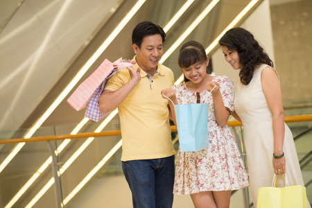 modern parents: Copy-spaced image of a modern family in the mall, parents presented their daughter with a gift Stock Photo