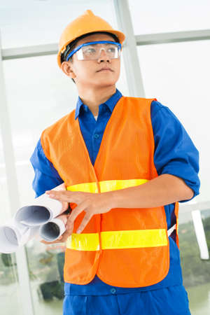Vertical image of a concentrated architect holding blueprints Stock Photo