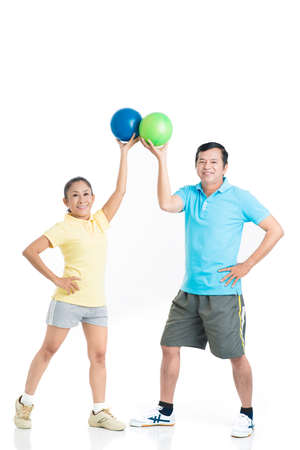 Portrait of two senior sportsmen with sports balls in hands