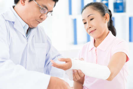 orthopedist: An adult doctor bandaging his patient in the hospital Stock Photo