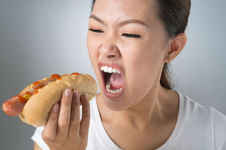 Asian girl devouring greedily a hot-dog 版權商用圖片