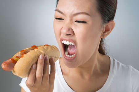 hot temper: Asian girl devouring greedily a hot-dog Foto de archivo