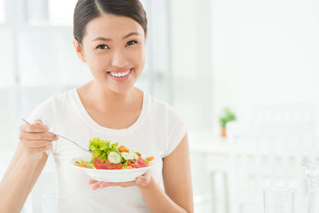 Portrait of a smiling beauty breakfasting with a vegetable salad Stock Photo
