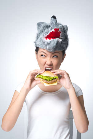 Vertical image of a girl in a wolf mask devouring a hamburger