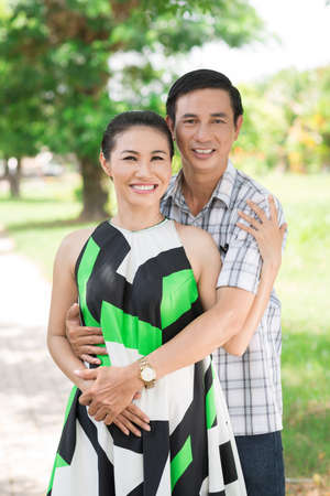 Vertical portrait of a middle-aged couple standing in the park