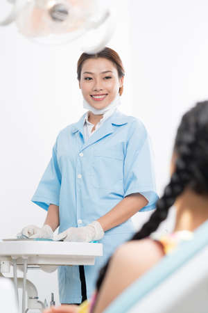 dentalcare: Image of a smiling dental assistant and back view of her patient sitting in the dental chair